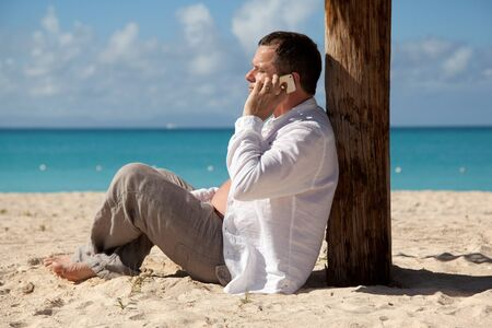 caribbean climate: man on the phone in the tropical beach