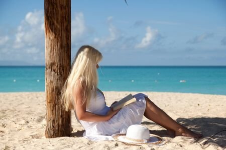 caribbean climate: girl with white dress reading book on the sunny beach Stock Photo
