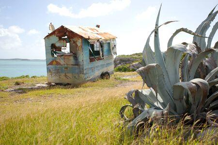 landscape mode: blue rusty trailer by the sea in Antigua