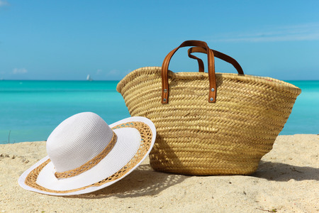 holiday destination: beach holiday background with white sand bag and hat