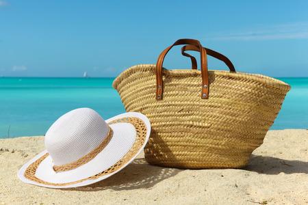 strandvakantie achtergrond met witte zand zak en hoed Stockfoto