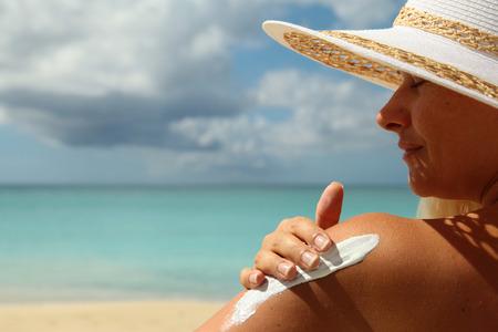 girl aplying  sun protection cream on the beach