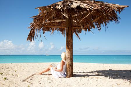 palm reading: girl reading book under palm leaf umbrella