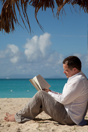 caribbean climate: man reading a book under pal leaf umbrella