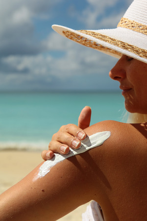 suncream: picture of women applying suncream on her shoulder Stock Photo
