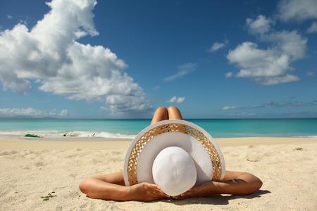 women sunbathing on the beach wearing white hat Foto de archivo