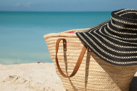 sun hat: striped blue sun hat on the beach bag