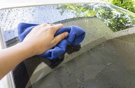 cleaning car: Mano con el azul de microfibra trapo de limpieza del coche
