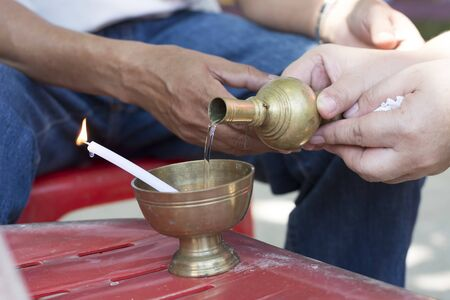 woman  hand: Buddhists man and woman hand ibation grail pouring water
