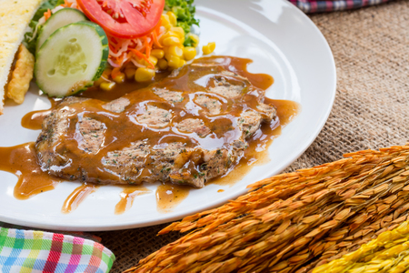 sack background: Beef steak with black pepper sauce , salad and French fries on sack background