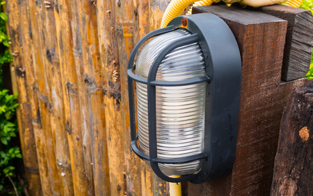 Outdoor lamp in garden with wooden Fence background.