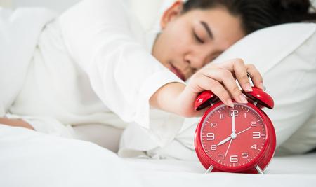 La donna asiatica spegne l'allarme. Mentre si dorme. Archivio Fotografico