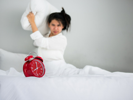 get tired: Asian woman throwing pillow towards on the red clock.