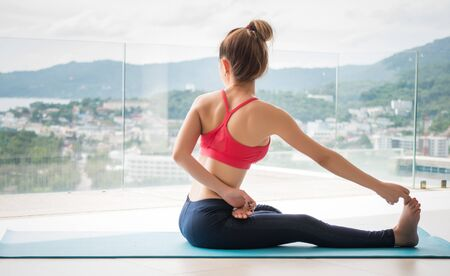 Healthy women wearing exercise clothes are playing yoga relaxation in janu sirsasana posture at  luxury clubhouse in healthy and yoga concept