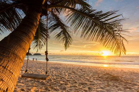 Woodden-Schwingen unter Kokosnussbaum auf dem Strand mit Sonnenunterganghintergrund