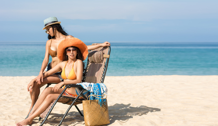 Lesbian couples or close friends are sitting on the beach While relaxing vacation or weekend on sunny days and nice weather in travel and holiday concept