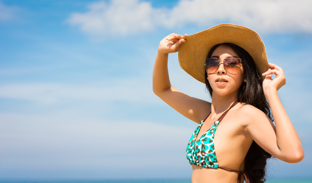 Asian woman on beach are posted to take a photo while happy vacation or weekend on sunny days and nice weather in travel and holiday concept