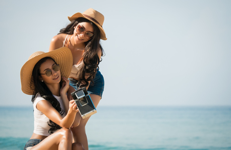 Couples lesbian or close friends use retro camea selfie or take photos for During a vacation On the tropical beach and blur sea background in travel and holiday concept,soft focus