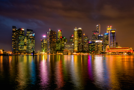 View of skyscraper in singapore city at night time with reflection in water in travel concept