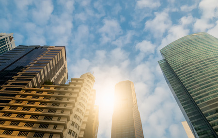 Skyscrapers in Singapores business district or the city centre with sunlight and cloud with blue sky background 報道画像