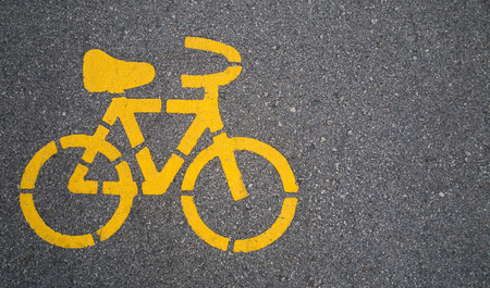 Top - view,Yellow bike symbol on the street in Urban city. transportation concept 写真素材