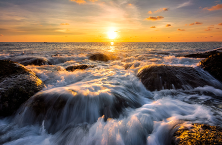 Seascape awesome wave on the rock with coloful sunset at beach in phuket thailand