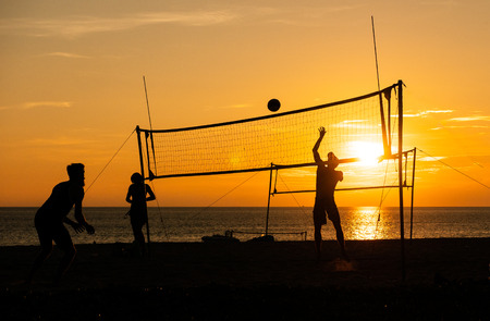 Group of silhouette tourists play volleyball on the tropical beach during the sunset time