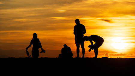 Groups of silhouette people Do activity on the beach on the Sunset  and show the posture during a vacation at the tropical beach in travel and holiday concept 写真素材