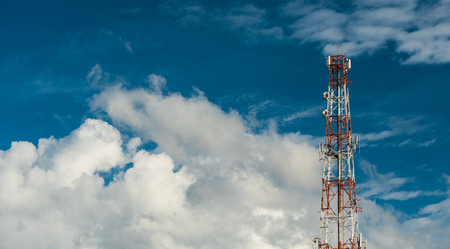 Telecommunication antenna on the top of the telecommunications service providers building with clouds and  blue sky background in technology concept
