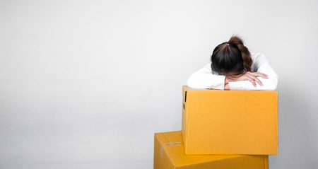 Woman sleeping on the box after moving home and moving the box 写真素材
