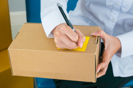 Start up owner small business with many parcel package are Writing customer Address before shipping with Check list paper at workplace online Selling concept