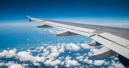 A view from the airplane window over the wings and engines  The planes are flying above the clouds and sky in transportation or travel concept