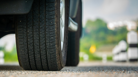 Close Up Car Tire Wheels on the road with blur road background
