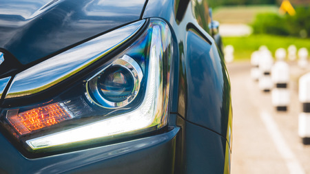 Close Up Halogen Car Headlights and LED light  From the front of the luxur car with blur road background in transportation concept