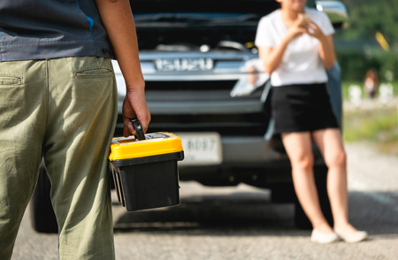 Car mechanic repair  Holding the toolbox in the hand with Women are calling for the car mechanic for assistance with car repair in Insurance and transportation concept