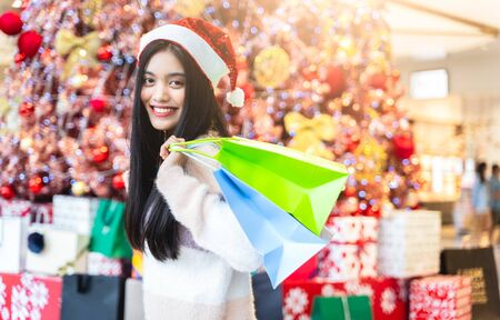 Asian women are shopping in the winter and Sale season In the hands are holding shopping bags and smiling with the Blur christmas tree background in shopping and travel concept.