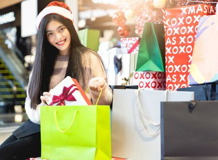 Asian women are put surprise gift to shopping bag on Christmas Day