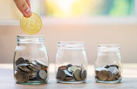 Money savings concepts hand holding bitcoin to put with coins in glass bottles to spend on expenses such as savings, tourism, investment, emergency, retirement on wooden table with blur background