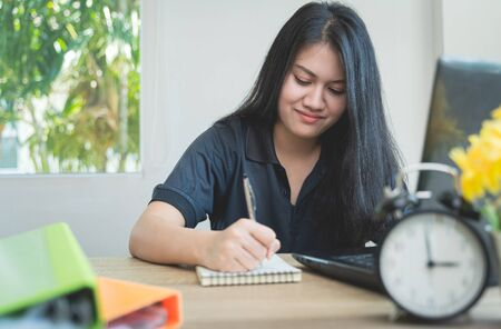 Work from home during the outbreak of the virus. Asian women sitting at sofa are working at home or online meeting, video conference and Writing data in a book in business concept at home office Imagens