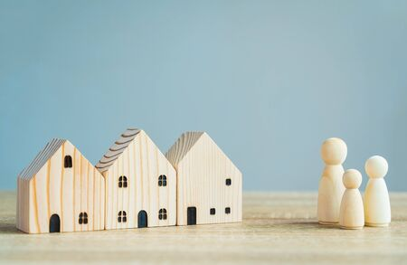 Money savings concepts. Wooden house models with family wooden dolls in meaning about saving money to buy a house, refinancing, investment or financial on wooden table with copy space