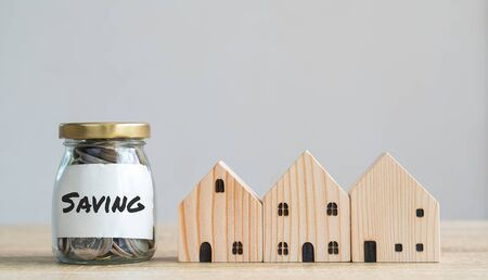 Money savings concepts. Wooden house models with coins in bottle and saving label meaning about saving money to buy a house, refinancing, investment or financial on wooden table with copy space Imagens