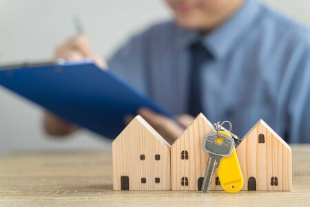 House Wooden model and Key in real estate , seller or buyer , loan concept with blur loan employee or realtor he's checking details about the sale of the house ,home Mortgage or home lone Imagens
