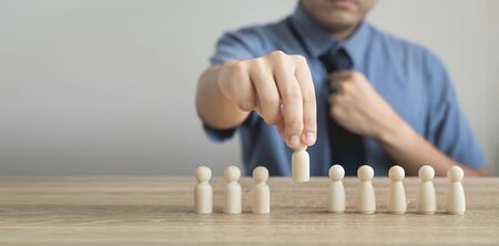 Owner is picking or select wood figure on the wooden roe in human resource management concepts Teamwork.Success Leadership,Business Progress and Competition on wood table and copy space