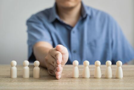 Men use barriers or blocks between wood figure Two groups that are fighting are ending the problem, finding a common solution, adjusting their understanding. In insurance concepts or quarrels