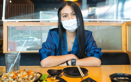 Women wear sanitary masks in restaurants. Women sit in front of the food at a Japanese restaurant serving New Normal, with barriers to social space and preventing the spread of corona virus