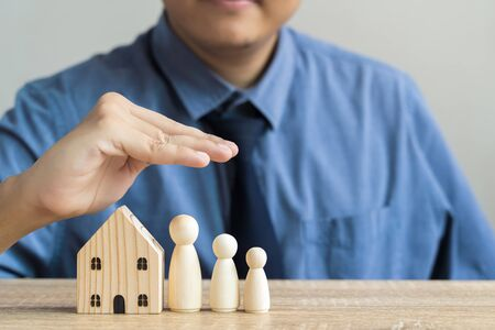 Insurance and Customer Care Concept A man who are brokers or customer care staff use their hands to protect wooden house model meaning care, protection. Loss protection or policy