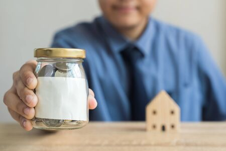 Money savings concepts  wood house models with blur Men are showing Glass bottel for saving money with blank label and blur wooden house on wooden table with blur background