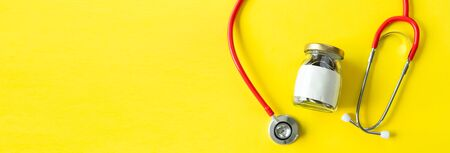 Banner of Savings and insurance concepts. Coins in a bottle with doctor headphones or red stethoscope. Saving for life insurance,retirement,health on the yellow background copy space