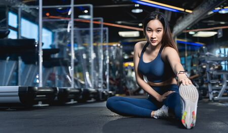 Asian women are sitting stretching their legs to stretch their muscles to warm up or cool down after a workout at fitness or gym with a patition barrier for social distancing in sport healthy concept