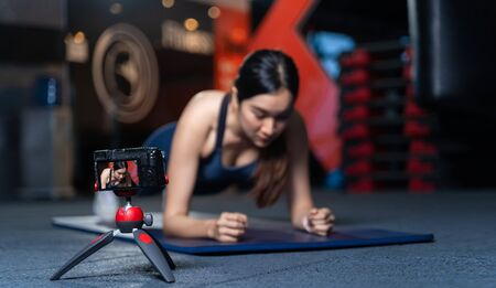 The camera on the tripod is taking pictures or videos. Asian Women Trainer In Good Shape Teaching or performing a sample of plank poses is a bodyweight exercise in online training concept Imagens